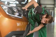 Ο μηχανικός στις πράσινες φόρμες προσπαθεί να απομακρύνει τον μπροστινό άχρηστο στοκ φωτογραφία με δικαίωμα ελεύθερης χρήσης