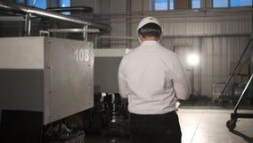 Ο μηχανικός στο σκληρό καπέλο κινείται μέσω ενός βαριού εργοστασίου βιομηχανίας με έναν υπολογιστή ταμπλετών r E απόθεμα βίντεο