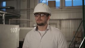 Ο μηχανικός στο σκληρό καπέλο κινείται μέσω ενός βαριού εργοστασίου βιομηχανίας με έναν υπολογιστή ταμπλετών r φιλμ μικρού μήκους