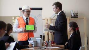 Ο μηχανικός της ασιατικής εμφάνισης εξηγεί στο γραφείο στους πελάτες τα χαρακτηριστικά γνωρίσματα της εργασίας, στα χέρια του μια φιλμ μικρού μήκους