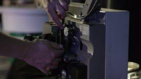 Ο μηχανικός χρεώνει την ταινία σε έναν παλαιό προβολέα ταινιών Κινηματογράφηση σε πρώτο πλάνο ενός εξελίκτρου με μια ταινία φιλμ μικρού μήκους