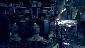 Ο μηχανισμός εργοστασίων σκληραίνει τα υαλώδη μπουκάλια και την απελευθέρωση τους επάνω στο μεταφορέα απόθεμα βίντεο