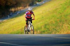 Ο μη αναγνωρισμένος τουρίστας οδηγά ένα ποδήλατο-ποδήλατο βουνών για να ταξιδεψει γύρω από τη δεξαμενή Phra κτυπήματος Στοκ Εικόνα