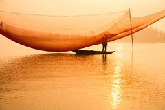 Ο μη αναγνωρισμένος ψαράς ελέγχει τα δίχτυα του στα ξημερώματα στον ποταμό σε Hoian, Βιετνάμ Στοκ Εικόνες