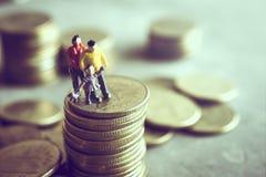 Ο μικροσκοπικοί μπαμπάς και τα παιδιά Mum που στέκονται πάνω από τα χρήματα σώζουν mon Στοκ Εικόνα