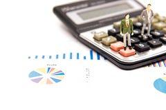 Ο μικροσκοπικός επιχειρηματίας ομάδας βλέπει την οικονομική γραφική παράσταση υπολογίζει επάνω τον πίνακα και τη σκέψη με το πρόγ στοκ φωτογραφία