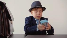 Ο μικρός επιχειρηματίας αγοριών στο κοστούμι βάζει τα τραπεζογραμμάτια εκατό-δολαρίων σε ένα πακέτο στον πίνακα στο γραφείο του απόθεμα βίντεο
