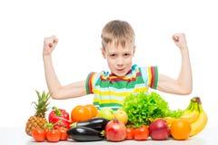 ο μικρός ισχυρός άνδρας παρουσιάζει δικέφαλους μυς στον πίνακα με έναν σωρό των φρέσκων λαχανικών και των φρούτων που απομονώνοντ στοκ φωτογραφίες