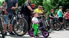 Ο μικρός ποδηλάτης στην έναρξη της ανακύκλωσης, που τρώει το αγόρι TAC σπασμού σε ένα μικρό ποδήλατο θα οδηγήσει με τους ενήλικου απόθεμα βίντεο