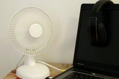 Ο μικρός φορητός επιτραπέζιος ανεμιστήρας στέκεται δίπλα σε ένα lap-top με τα ασύρματα ακουστικά που κρεμούν στη μαύρη οθόνη στοκ εικόνα με δικαίωμα ελεύθερης χρήσης
