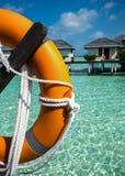 Ο μισός από πορτοκαλή lifebuoy στο πρώτο πλάνο στη θάλασσα και τα μπανγκαλόου backg Στοκ φωτογραφία με δικαίωμα ελεύθερης χρήσης