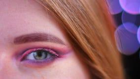 Ο μισός βλαστός προσώπου κινηματογραφήσεων σε πρώτο πλάνο του νέου ελκυστικού καυκάσιου θηλυκού με το ρόδινο όμορφο ροζ ακτινοβολ απόθεμα βίντεο