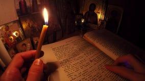 Ο μοναχός διαβάζει τη Βίβλο και προσεύχεται πριν από τα εικονίδια με τα κεριά απόθεμα βίντεο