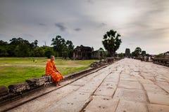 Ο μοναχός κάθεται στο υπερυψωμένο μονοπάτι του ναού Angkor Wat Στοκ φωτογραφία με δικαίωμα ελεύθερης χρήσης