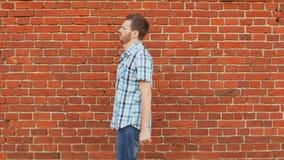 Ο μοντέρνος γενειοφόρος τύπος που φορά το πουκάμισο και τα τζιν πηγαίνει κατά μήκος του τουβλότοιχος απόθεμα βίντεο