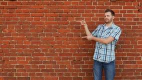 Ο μοντέρνος γενειοφόρος τύπος που φορά το πουκάμισο και τα τζιν δείχνει το διάστημα αντιγράφων, υπόβαθρο τουβλότοιχος απόθεμα βίντεο