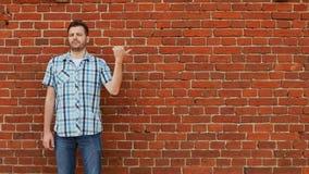 Ο μοντέρνος γενειοφόρος τύπος που φορά το πουκάμισο και τα τζιν δείχνει το διάστημα αντιγράφων, υπόβαθρο τουβλότοιχος φιλμ μικρού μήκους