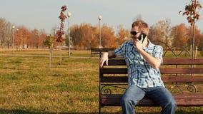 Ο μοντέρνος γενειοφόρος τύπος στα γυαλιά ηλίου κάθεται σε έναν πάγκο και την ομιλία στο τηλέφωνο απόθεμα βίντεο