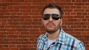 Ο μοντέρνος γενειοφόρος τύπος στα γυαλιά ηλίου που φορούν το πουκάμισο εξετάζει τη κάμερα απόθεμα βίντεο
