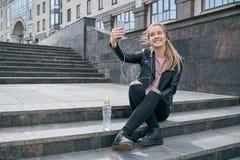 Ο μοντέρνος μακρυμάλλης νέος χαμογελώντας έφηβος κοριτσιών σε ένα σχισμένα τζιν δέρματος σακάκι και κάνει ένα selfie στοκ φωτογραφία με δικαίωμα ελεύθερης χρήσης