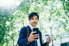 Ο μοντέρνος νέος επιχειρηματίας που χρησιμοποιεί το smartphone για η μουσική περπατώντας στο πάρκο πόλεων και κρατώντας παίρνει μ Στοκ Εικόνες