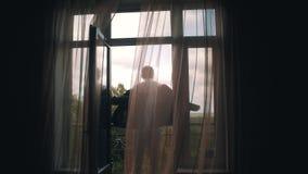 Ο μοντέρνος νέος τύπος βάζει σε ένα σακάκι που στέκεται στο μπαλκόνι Όμορφη άποψη από το δωμάτιο μέσω της κουρτίνας πίσω από τον  φιλμ μικρού μήκους