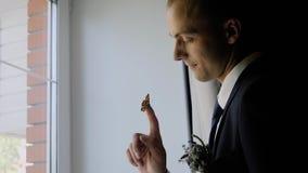 Ο μοντέρνος νέος τύπος βάζει σε ένα σακάκι που στέκεται στο μπαλκόνι Όμορφη άποψη από το δωμάτιο μέσω της κουρτίνας πίσω από τον  απόθεμα βίντεο