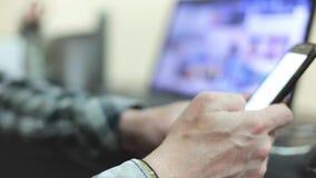 Ο μοντέρνος νεαρός άνδρας σε ένα πουκάμισο καρό χρησιμοποιεί ένα smartphone απόθεμα βίντεο