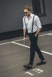 Ο μοντέρνος νεαρός άνδρας στα γυαλιά ηλίου που καπνίζουν περπατώντας με παραδίδει την τσέπη Στοκ φωτογραφία με δικαίωμα ελεύθερης χρήσης