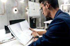 Ο μοντέρνος σκοτεινός-μαλλιαρός αρχιτέκτονας στα γυαλιά και σε μια μπλε ζακέτα εργάζεται με τα έγγραφα στο γραφείο στο γραφείο στοκ εικόνες