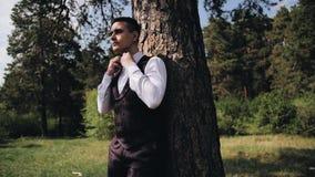 Ο μοντέρνος τύπος σε ένα άσπρες πουκάμισο και μια φανέλλα στέκεται στα ξύλα από ένα δέντρο και ισιώνει το δεσμό του Όμορφος νεαρό φιλμ μικρού μήκους
