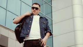 Ο μοντέρνος τύπος σε ένα σακάκι τζιν και ένα σακίδιο πλάτης στον ώμο το απόθεμα βίντεο