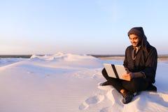 Ο μορφωμένος αραβικός σπουδαστής χρησιμοποιεί το lap-top και απασχολείται στη συνεδρίαση στην άμμο ανάμεσα στοκ φωτογραφίες με δικαίωμα ελεύθερης χρήσης