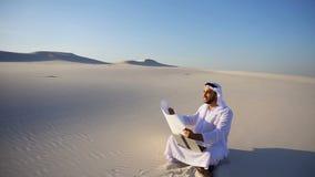 Ο μορφωμένος αρσενικός μουσουλμανικός αραβικός Sheikh Ε.Α.Ε. αρχιτέκτονας κάθεται με τη συσκευή και το σχέδιο στα χέρια, εξετάζει απόθεμα βίντεο