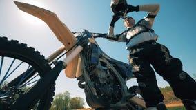 Ο μοτοσυκλετιστής βγάζει το κράνος του και το κρεμά στο sportbike του φιλμ μικρού μήκους