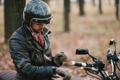 Ο μοτοσυκλετιστής κάθεται σε μια παλαιά μοτοσικλέτα καφές-δρομέων, υπόβαθρο φθινοπώρου Στοκ Φωτογραφίες