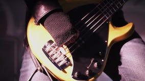 Ο μουσικός έντυσε στη μαύρη βαθιά κιθάρα παιχνιδιών σακακιών δέρματος passionatle στη σκηνή απόθεμα βίντεο