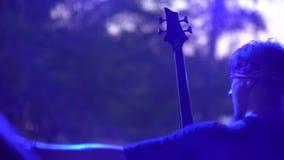 Ο μουσικός βράχου παίζει την ηλεκτρική κιθάρα από τη σκηνή σε μια συναυλία κινηματογράφηση σε πρώτο πλάνο χεριών κάτω από το επίκ απόθεμα βίντεο