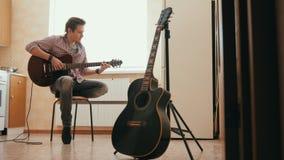 Ο μουσικός νεαρών άνδρων συνθέτει τη μουσική στην κιθάρα και παίζει στην κουζίνα, άλλο μουσικό όργανο στο πρώτο πλάνο, απόθεμα βίντεο