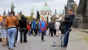 Ο μουσικός οδών με ένα ακκορντέον παίζει και τραγουδά τα τραγούδια στη γέφυρα του Charles, Πράγα, Δημοκρατία της Τσεχίας απόθεμα βίντεο