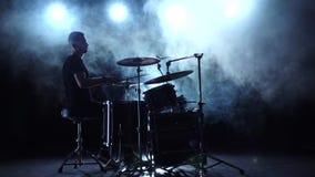 Ο μουσικός παίζει επαγγελματικά την καλή μουσική στα τύμπανα χρησιμοποιώντας τα ραβδιά ανασκόπηση καπνώδης σκιαγραφία κίνηση αργή απόθεμα βίντεο