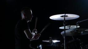 Ο μουσικός παίζει επαγγελματικά την καλή μουσική στα τύμπανα χρησιμοποιώντας τα ραβδιά Μαύρη ανασκόπηση σκιαγραφία απόθεμα βίντεο