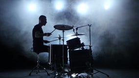 Ο μουσικός παίζει επαγγελματικά την καλή μουσική στα τύμπανα χρησιμοποιώντας τα ραβδιά ανασκόπηση καπνώδης σκιαγραφία απόθεμα βίντεο