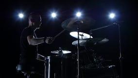 Ο μουσικός παίζει επαγγελματικά τη μουσική στα τύμπανα Μαύρη ανασκόπηση Πλάγια όψη πίσω φως σκιαγραφία κίνηση αργή απόθεμα βίντεο