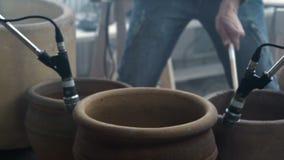 Ο μουσικός παίζει τα ξύλινα ραβδιά στα μεγάλα κεραμικά δοχεία στο εργαστήριο αγγειοπλαστικής απόθεμα βίντεο
