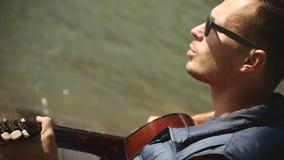 Ο μουσικός παίζει την κιθάρα στην όχθη ποταμού απόθεμα βίντεο