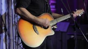 Ο μουσικός παίζει την κιθάρα, το χέρι και τα δάχτυλα του κιθαρίστα, ο κιθαρίστας με την κιθάρα στο υπόβαθρο απόθεμα βίντεο