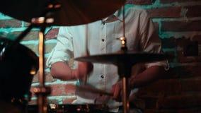 Ο μουσικός σε ένα άσπρο παιχνίδι πουκάμισων παίζει τύμπανο για μια απόδοση σε έναν φραγμό τζαζ φιλμ μικρού μήκους