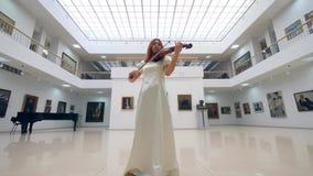 Ο μουσικός σε ένα άσπρο φόρεμα παίζει το βιολί στην αίθουσα τέχνης φιλμ μικρού μήκους