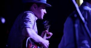 Ο μουσικός στην κιθάρα παιχνιδιών καπέλων στη λέσχη νύχτας, κλείνει επάνω απόθεμα βίντεο